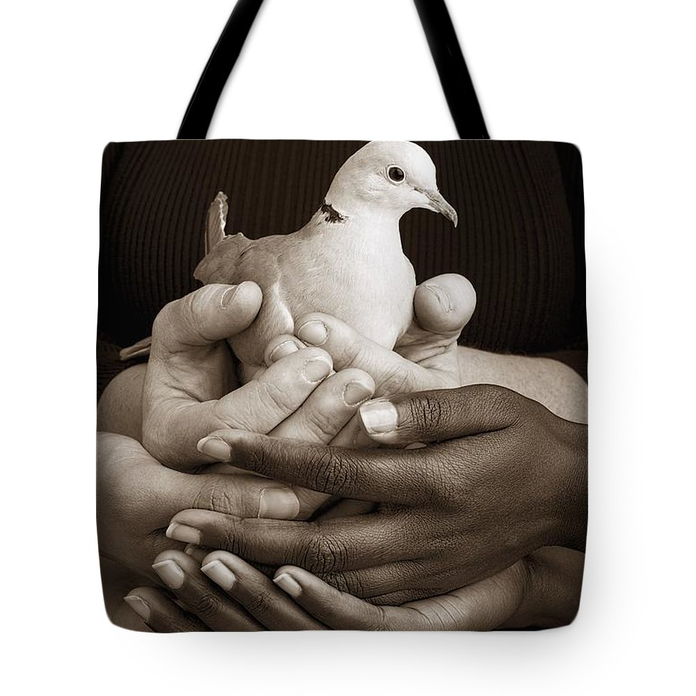 Teamwork Tote Bag featuring the photograph Many Hands Holding A Dove by Ron Nickel