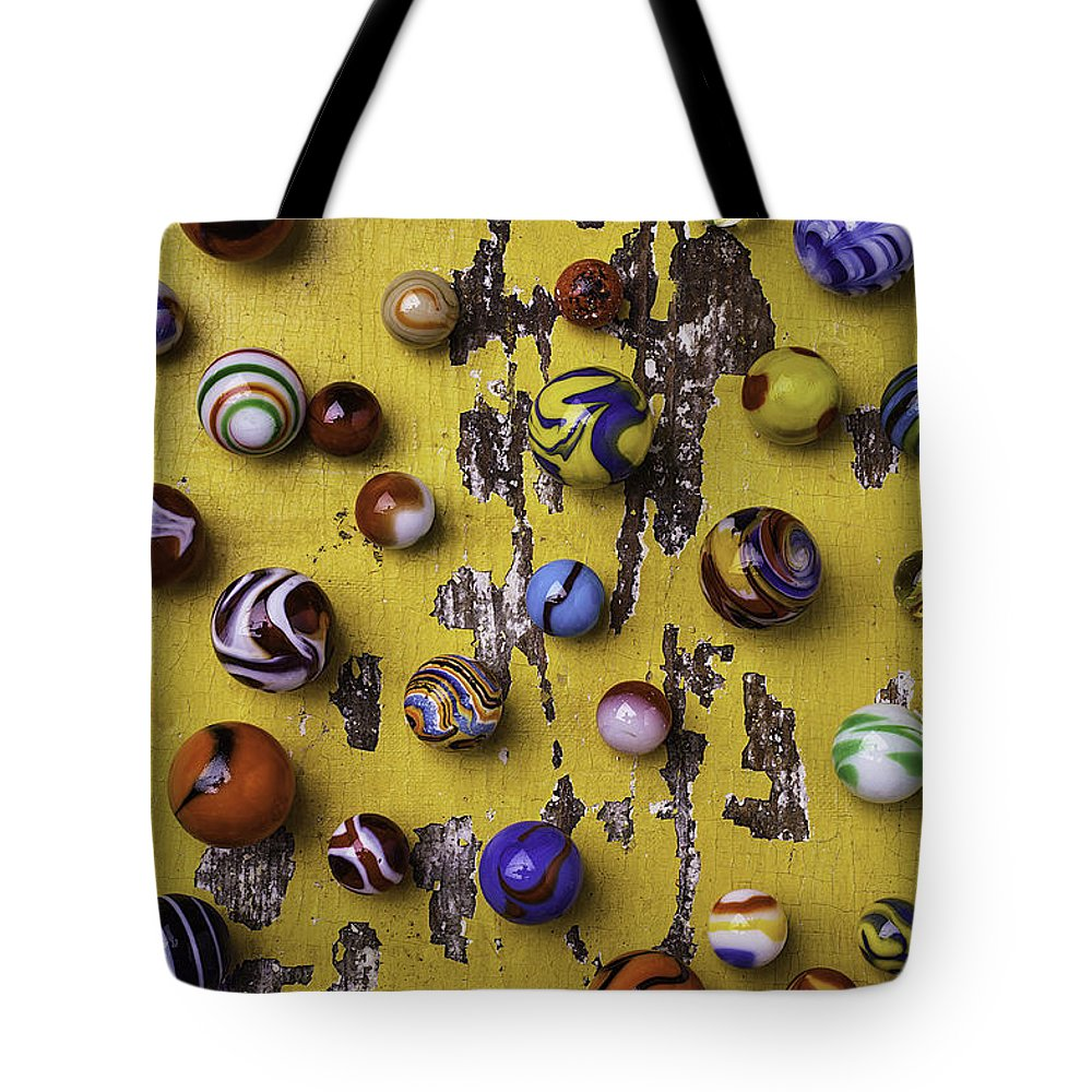 Marbles Tote Bag featuring the photograph Marbles On Yellow Wooden Table by Garry Gay