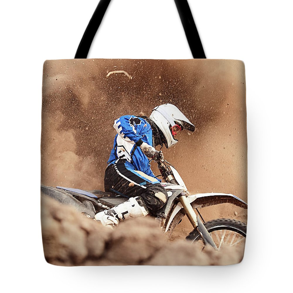 Crash Helmet Tote Bag featuring the photograph Motocross Biker Taking A Turn In The by Daniel Milchev