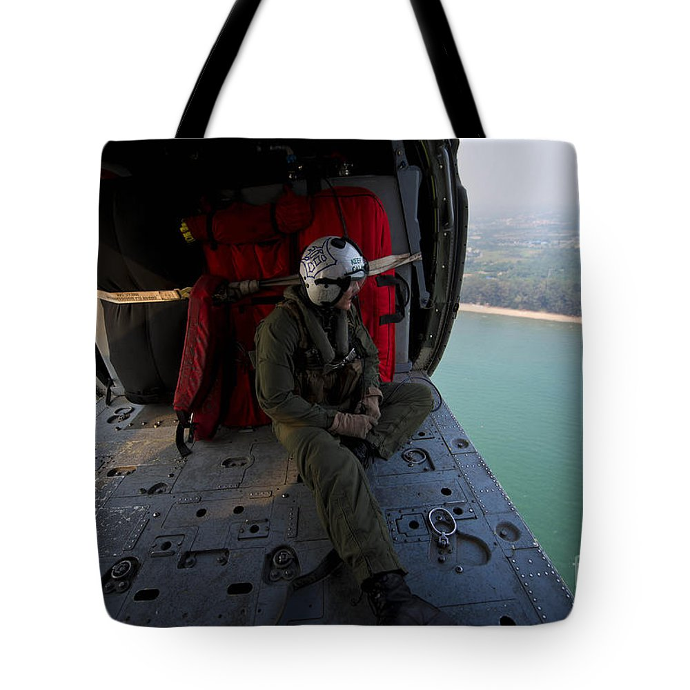 Military Tote Bag featuring the photograph Naval Aircrewman Surveys The Gulf by Stocktrek Images