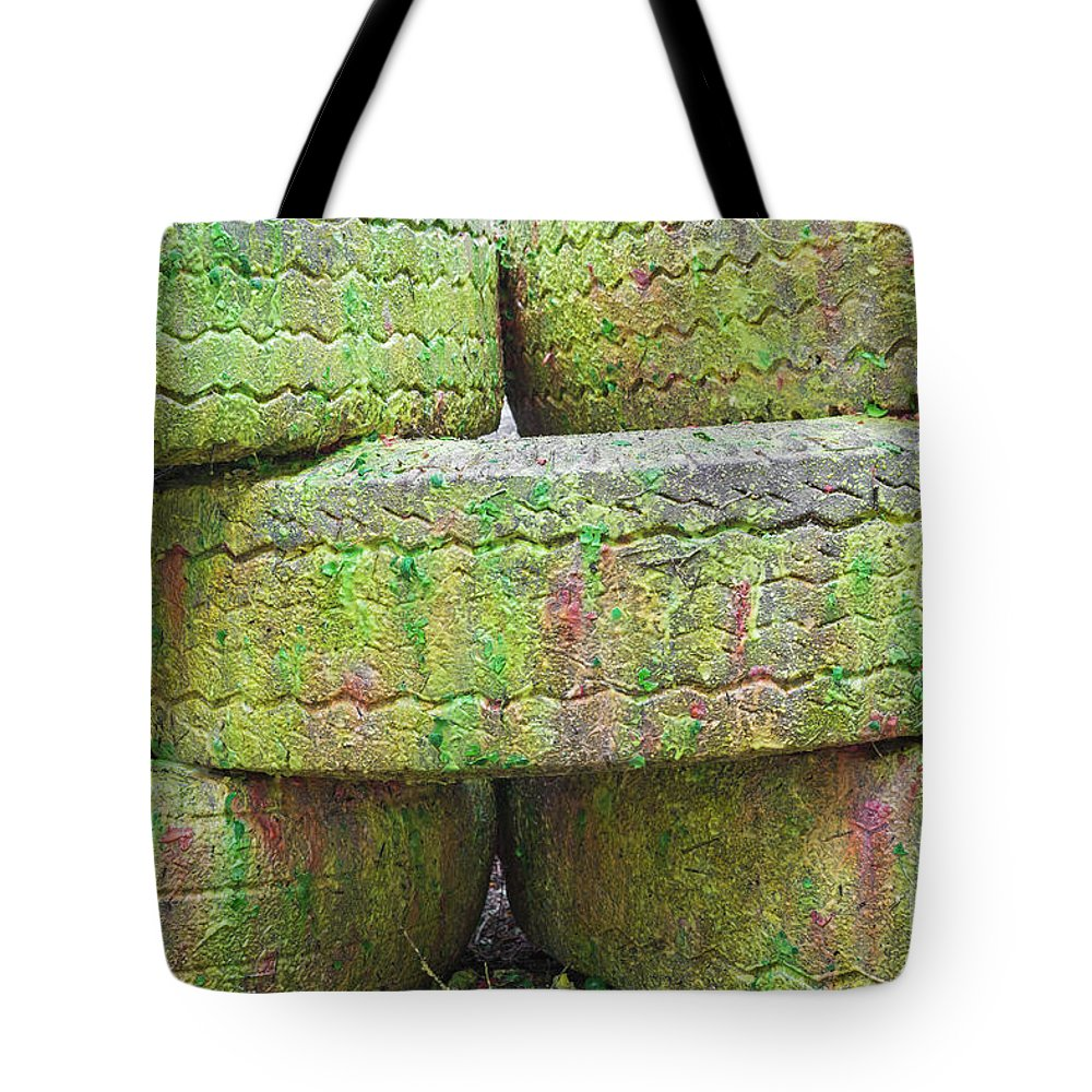 Bad Condition Tote Bag featuring the photograph Paint Covered Barricade Made Of Tires On Paintball Field by Bryan Mullennix
