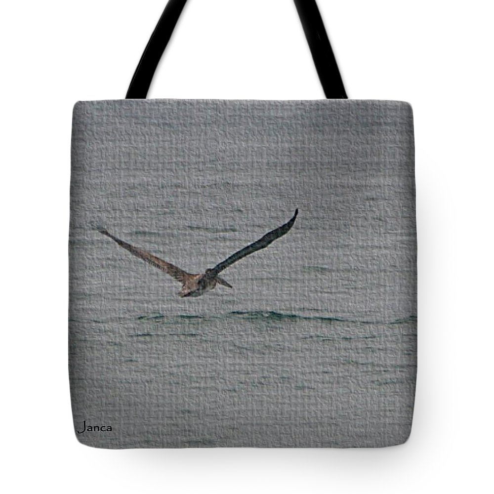 Pelican Flying Low Tote Bag featuring the photograph pelican Flying Low by Tom Janca