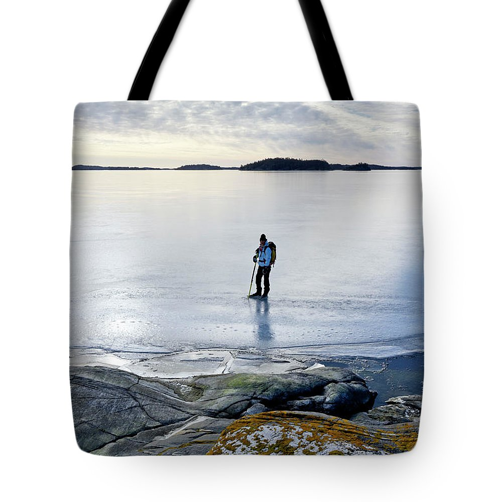 Archipelago Tote Bag featuring the photograph Person Skating At Frozen Sea by Johner Images