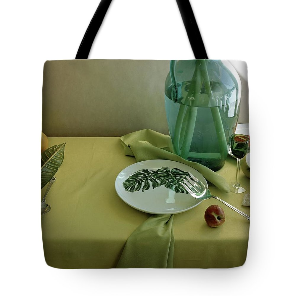 Table Setting Tote Bag featuring the photograph Plates, Apples And A Vase On A Green Tablecloth by Horst P. Horst