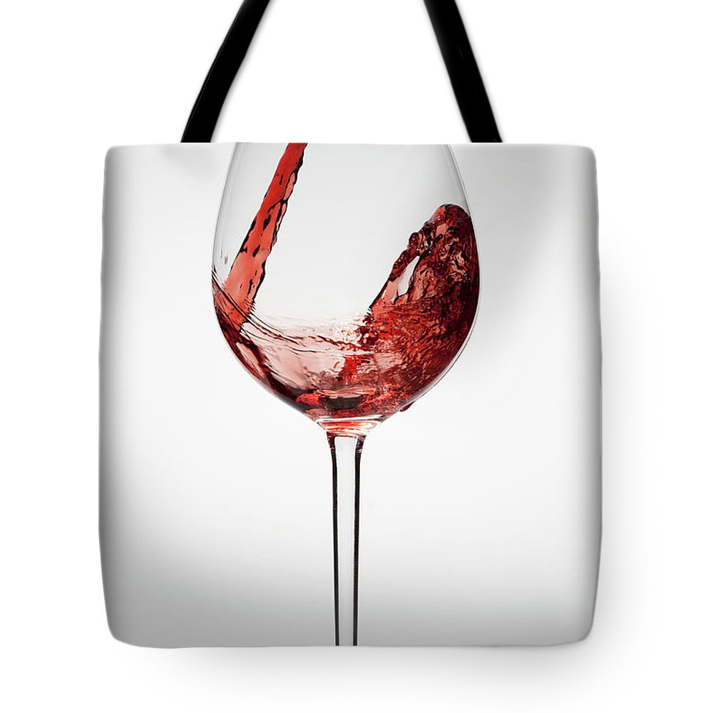 Alcohol Tote Bag featuring the photograph Red Wine Being Poured Into A Glass by Dual Dual
