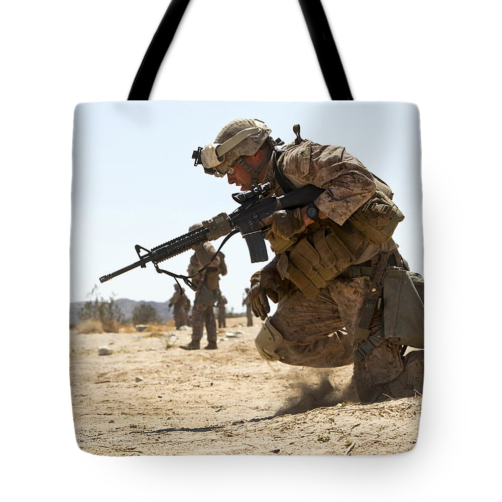 Military Tote Bag featuring the photograph Rifleman Kneels To The Ground While by Stocktrek Images