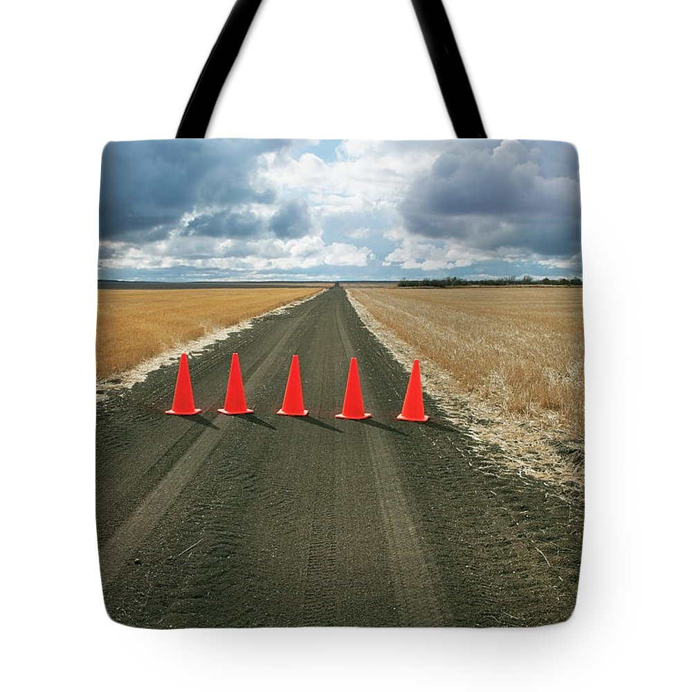 Orange Color Tote Bag featuring the photograph Safety Cones Lined Up Across A Rural by Benjamin Rondel / Design Pics