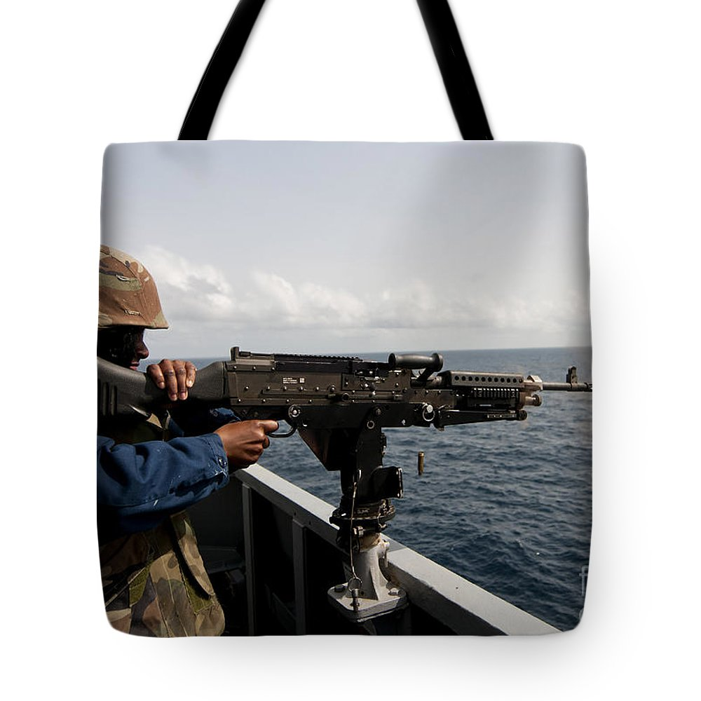 Military Tote Bag featuring the photograph Sailor Fires A M240b Machine Gun Aboard by Stocktrek Images