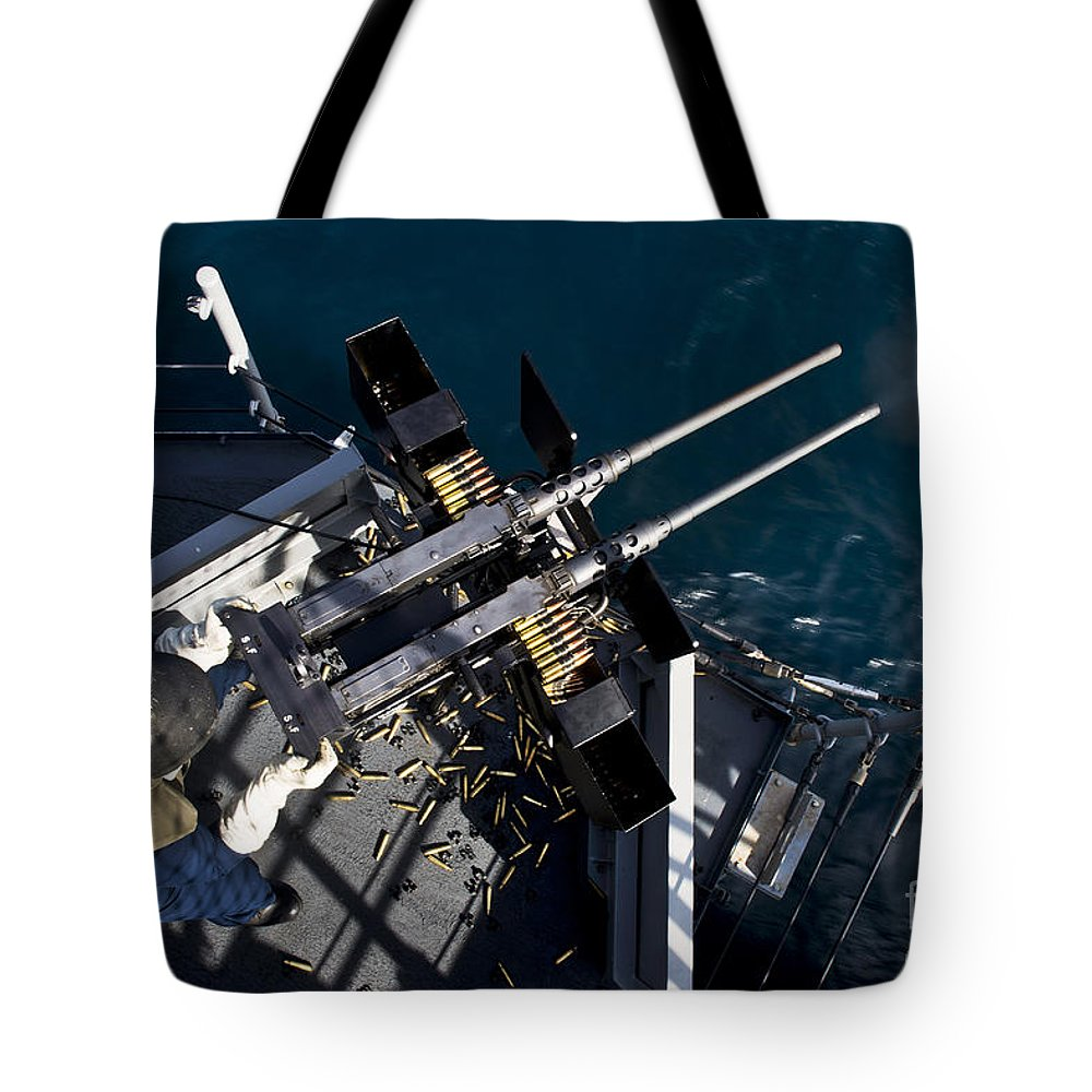 Military Tote Bag featuring the photograph Seaman Fires Twin .50 Caliber Machine by Stocktrek Images