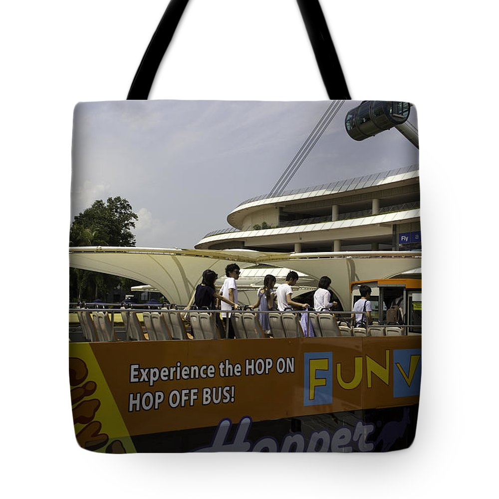 Action Tote Bag featuring the photograph Singapore Flyer Along With The Sight-seeing Bus That Takes Tourists Around The City by Ashish Agarwal