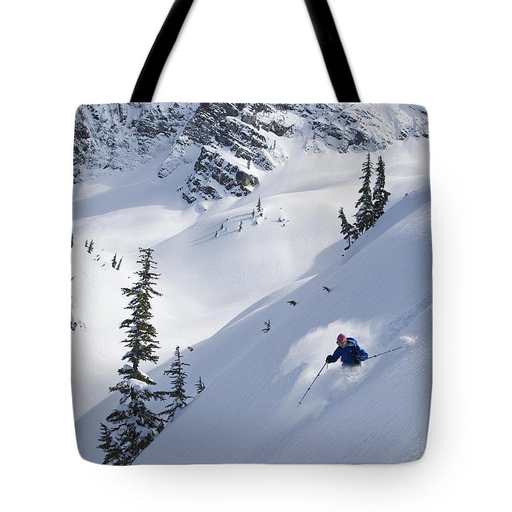 Light Tote Bag featuring the photograph Skier Hitting Powder Below Nak Peak by Kurt Werby