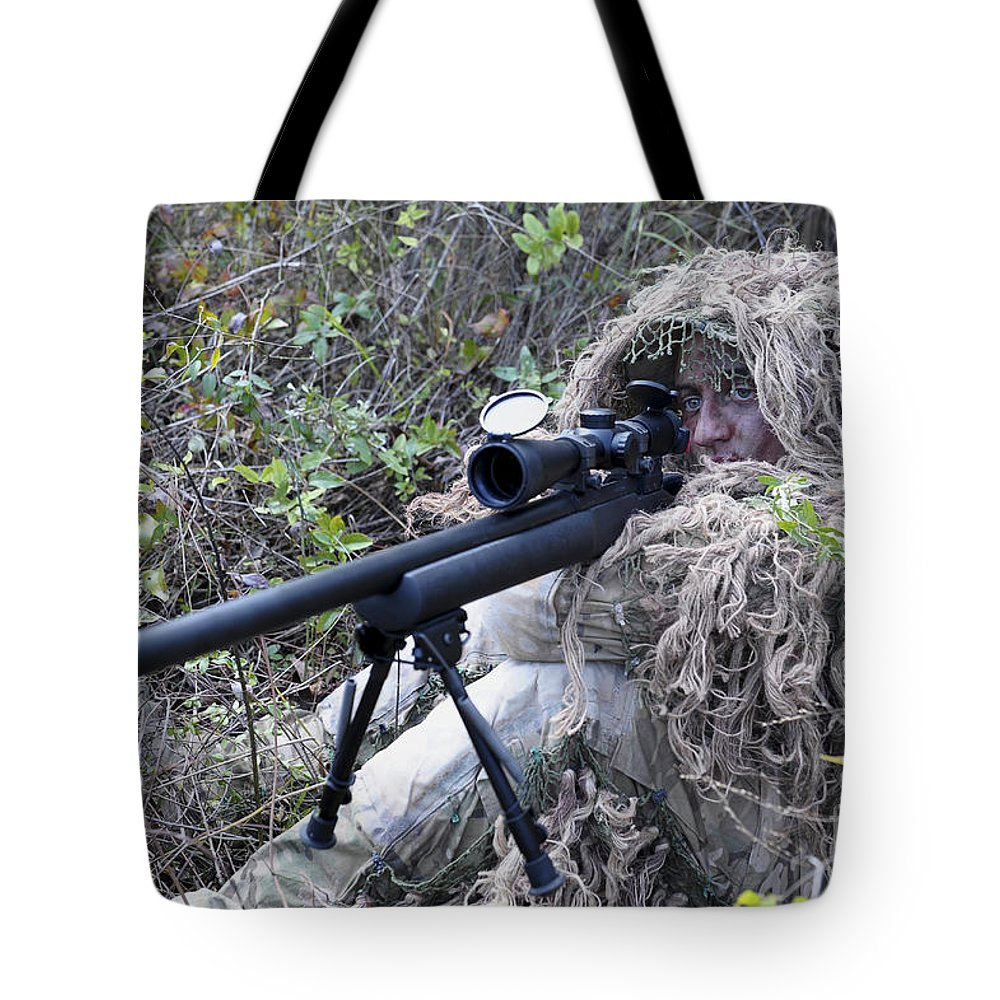 Military Tote Bag featuring the photograph Sniper Dressed In A Ghillie Suit by Stocktrek Images