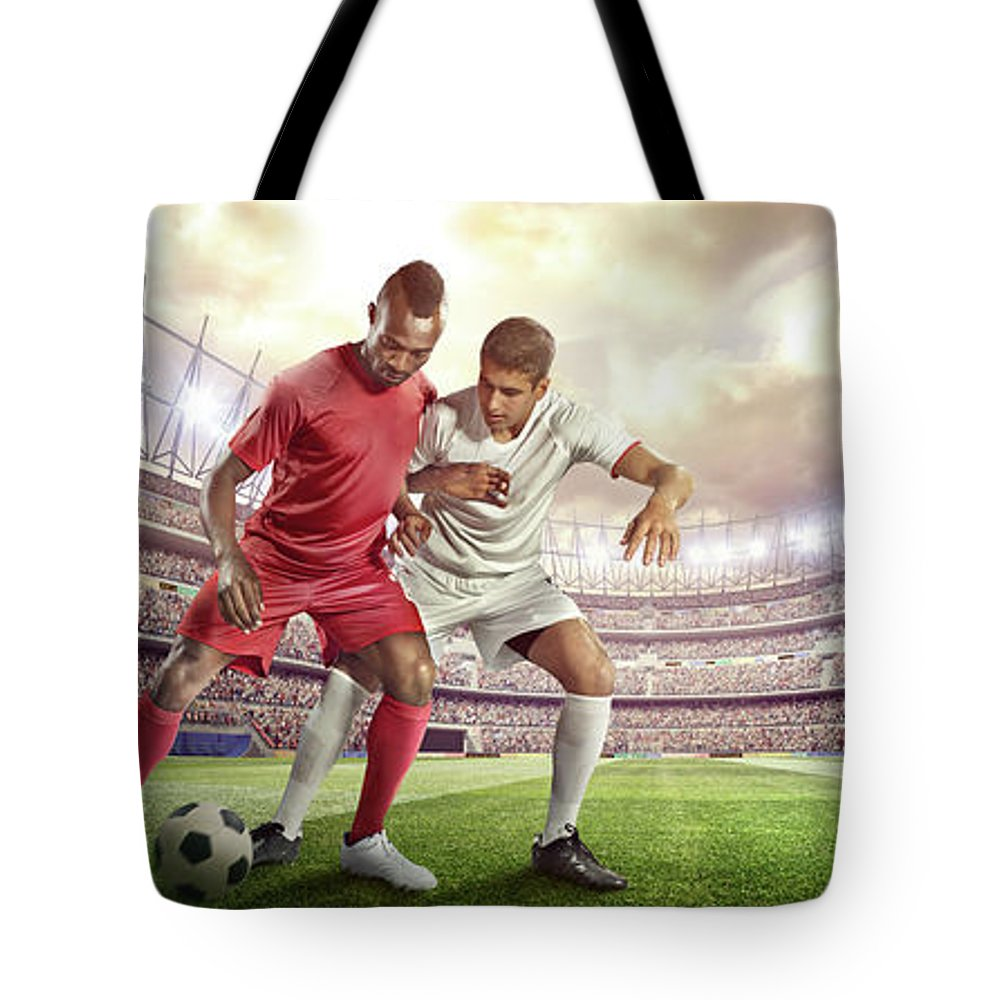 Soccer Uniform Tote Bag featuring the photograph Soccer Player Tackling Ball In Stadium by Dmytro Aksonov