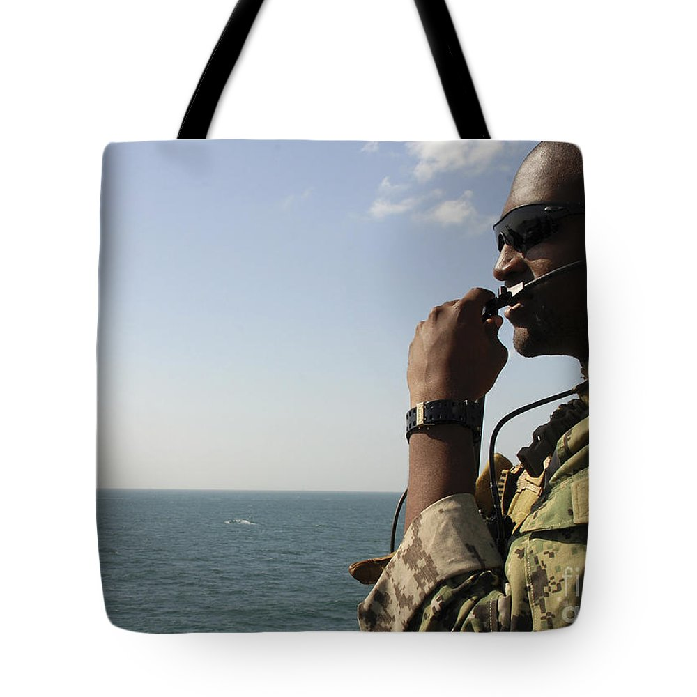 Military Tote Bag featuring the photograph Soldier Instructs Small Boat Maneuvers by Stocktrek Images