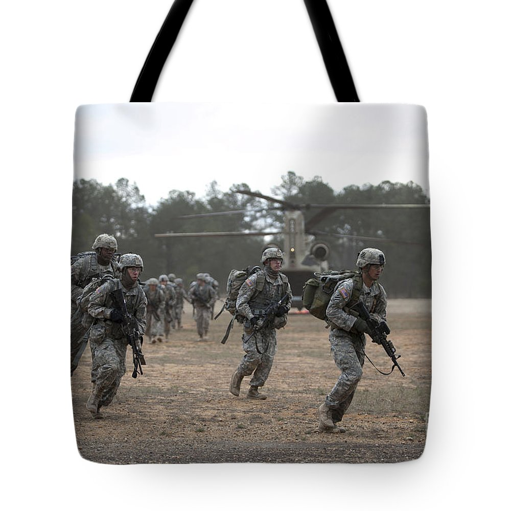 Fort Benning Tote Bag featuring the photograph Soldiers Exit A Ch-47 Chinook by Stocktrek Images
