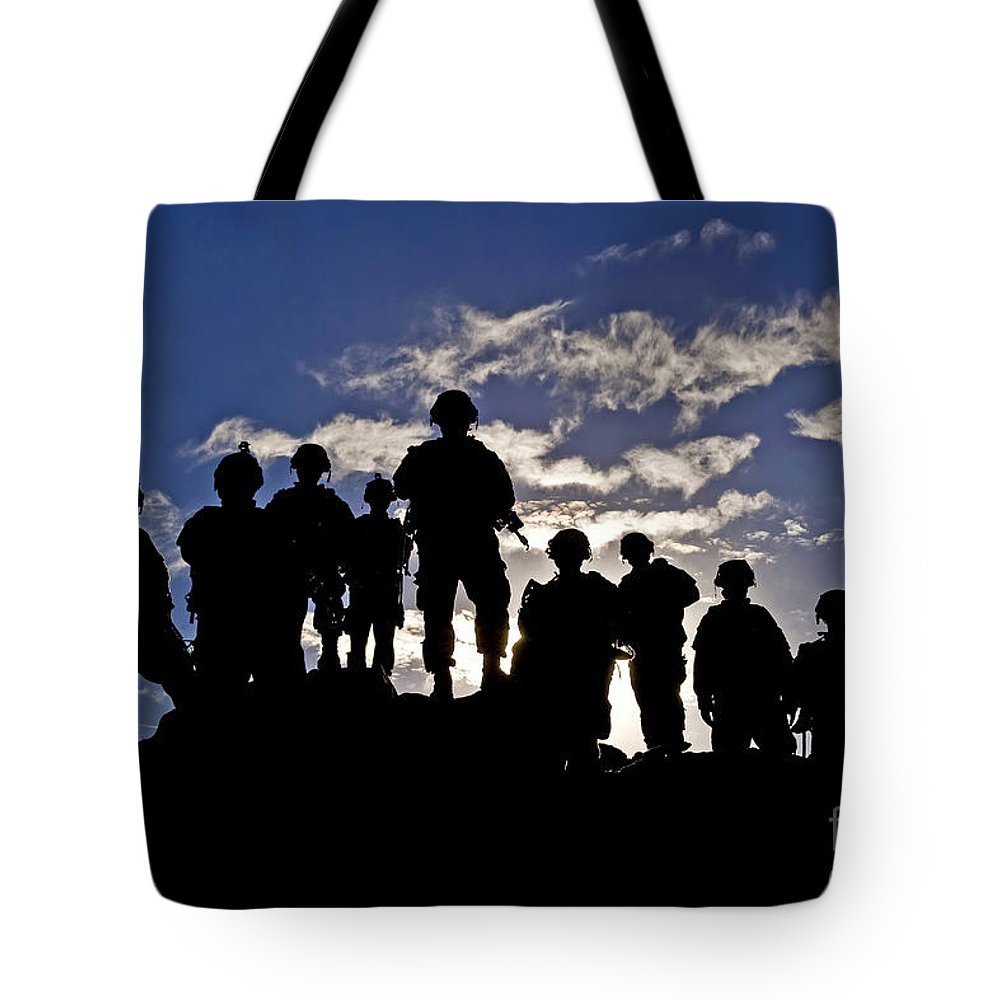 National Training Center Tote Bag featuring the photograph Soldiers Watch Troop Movements At Fort by Stocktrek Images