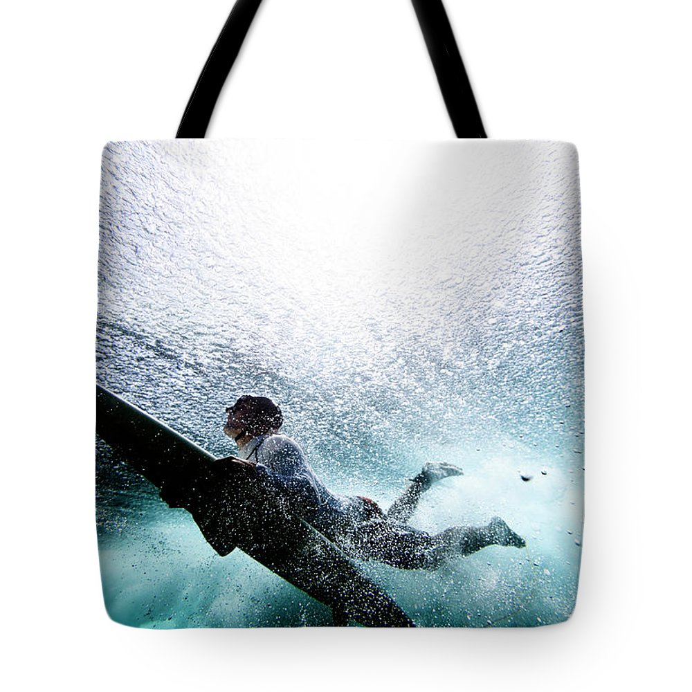 Expertise Tote Bag featuring the photograph Surfer Duck Diving by Subman