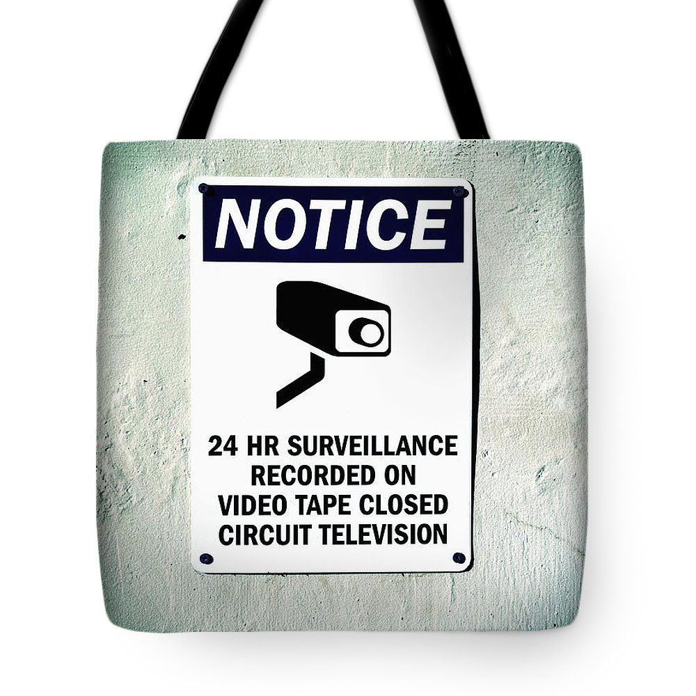 Area Tote Bag featuring the photograph Surveillance Sign On Concrete Wall by Bryan Mullennix