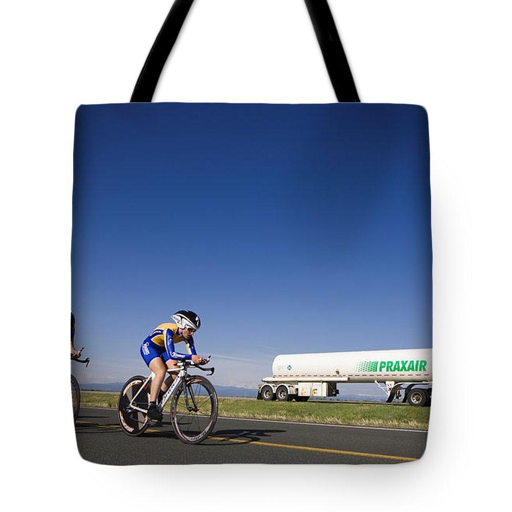 Cycling Tote Bag featuring the photograph Team Time Trial Chasing A Tanker Truck by Jason O Watson