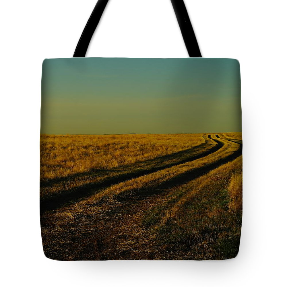 Northeast Montana Tote Bag featuring the photograph That Long Long Road by Jeff Swan