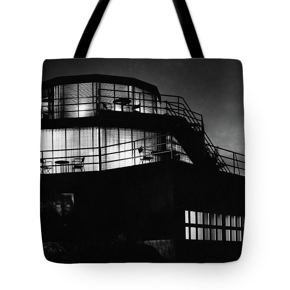 Home Tote Bag featuring the photograph The Exterior Of A Spiral House Design At Night by Eugene Hutchinson