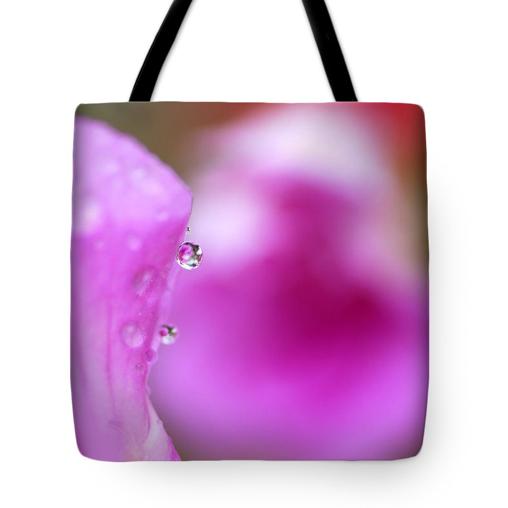 Flower Tote Bag featuring the photograph The Flower Enclosed In A Small Drop Of Water by Guido Montanes Castillo