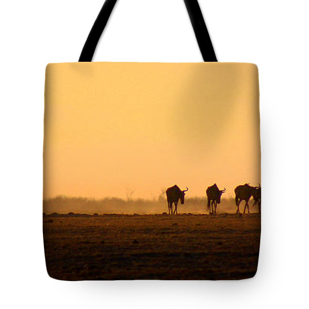 Wildebeests Tote Bag featuring the photograph The Straggler by Amanda Stadther