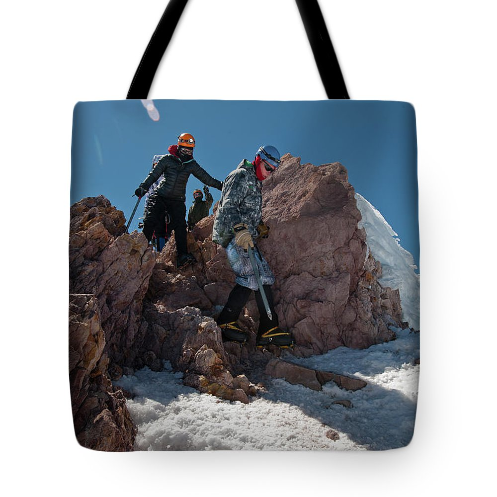 Young Man Tote Bag featuring the photograph Three People Climb Down Rocks by Beth Wald
