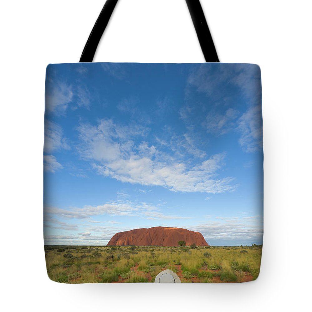 00477467 Tote Bag featuring the photograph Tourist And Clouds At Ayers Rock by Yva Momatiuk John Eastcott
