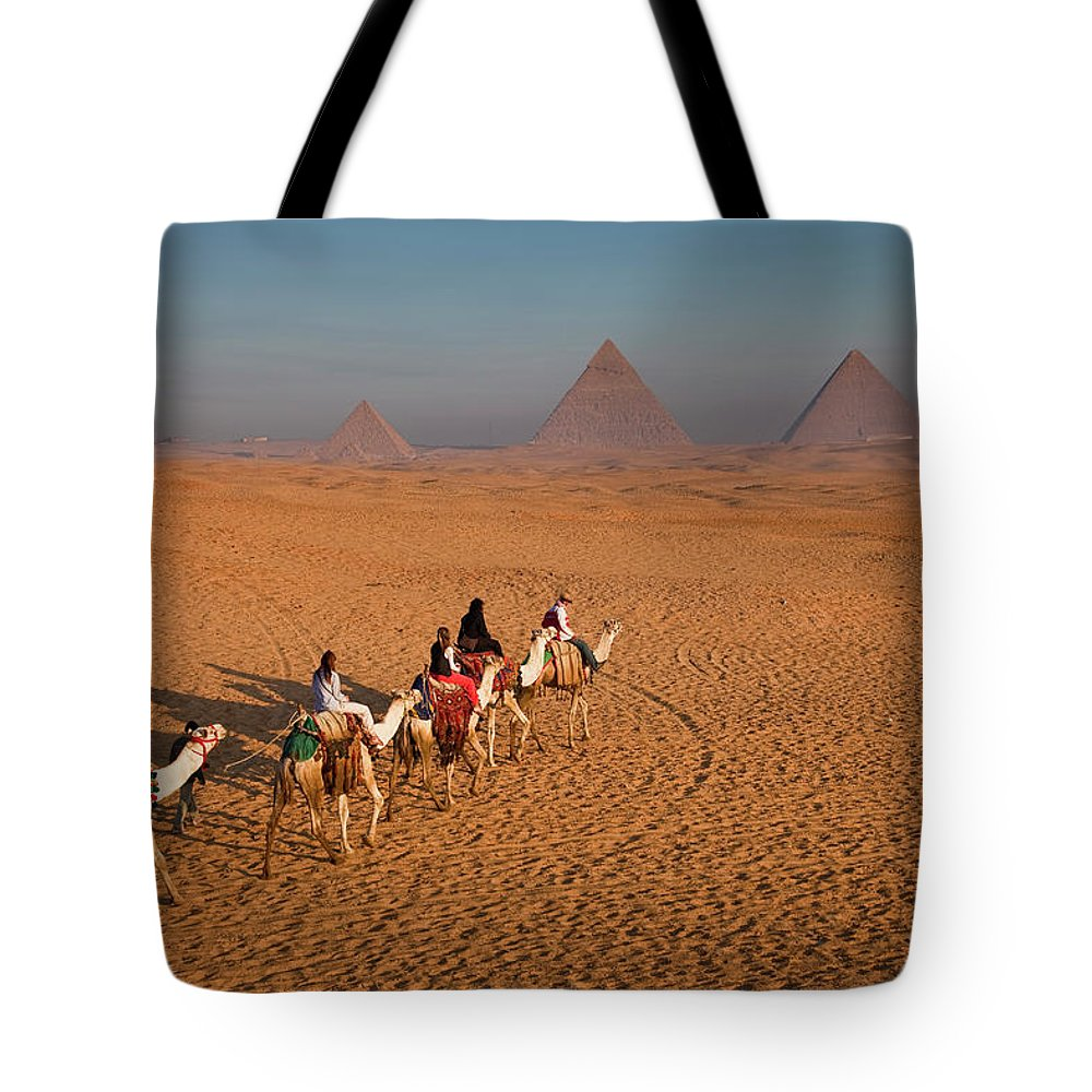 Working Animal Tote Bag featuring the photograph Tourists On Camels & Pyramids Of Giza by Richard I'anson