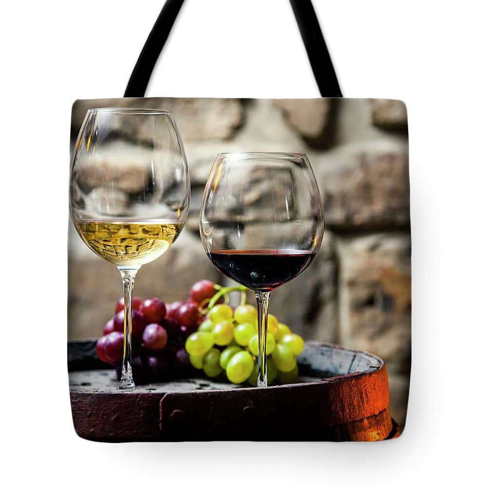 Alcohol Tote Bag featuring the photograph Two Glasses Of Red And White Wine In by Piranka