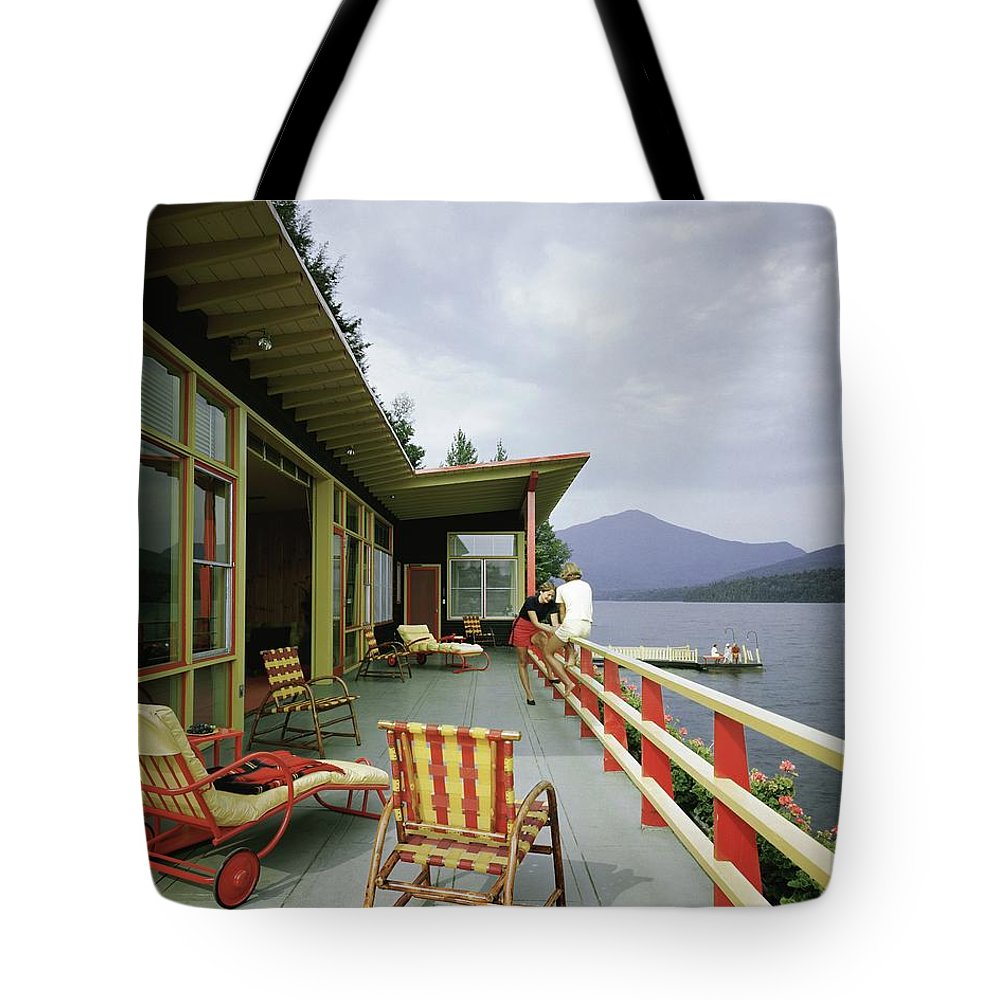 Alfred Rose Tote Bag featuring the photograph Two Women On The Deck Of A House On A Lake by Robert M. Damora