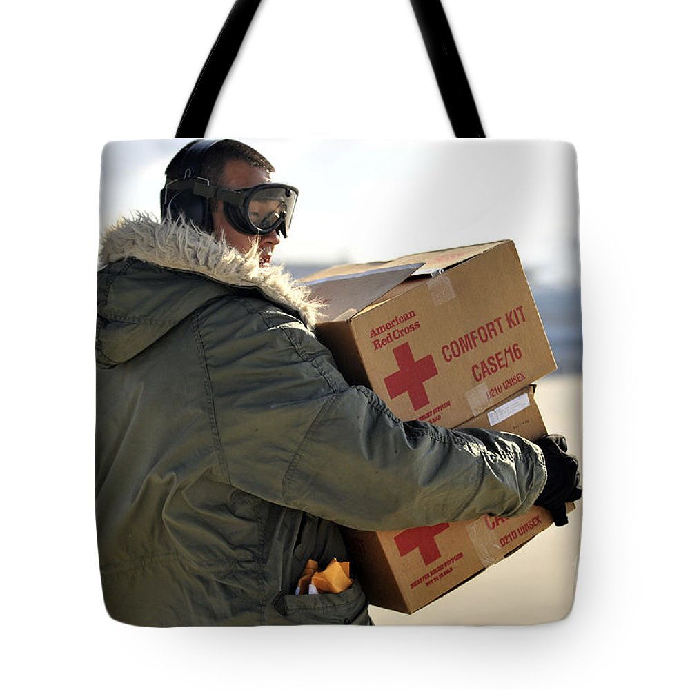 Us Air Force Tote Bag featuring the photograph U.s. Air Force Airman Carries American by Stocktrek Images