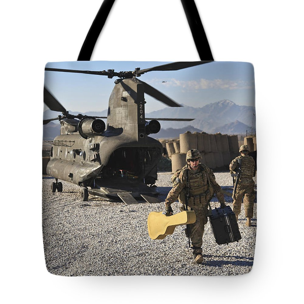 Middle East Tote Bag featuring the photograph U.s. Army Sergeant Helps Unload Band by Stocktrek Images