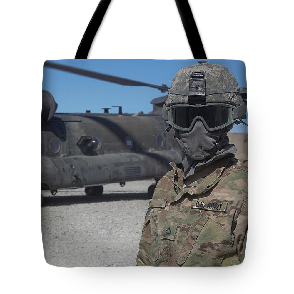 Protective Eyewear Tote Bag featuring the photograph U.s. Army Soldier Stands Ready To Load by Stocktrek Images