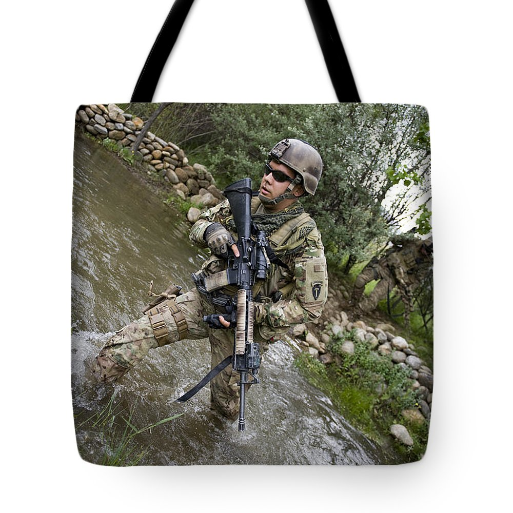 Middle East Tote Bag featuring the photograph U.s. Army Soldier Walks Through A Creek by Stocktrek Images