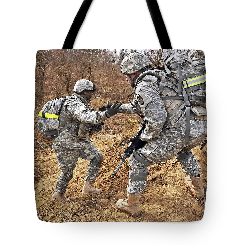 Grafenwoehr Training Area Tote Bag featuring the photograph U.s. Army Soldiers Helps A Fellow by Stocktrek Images