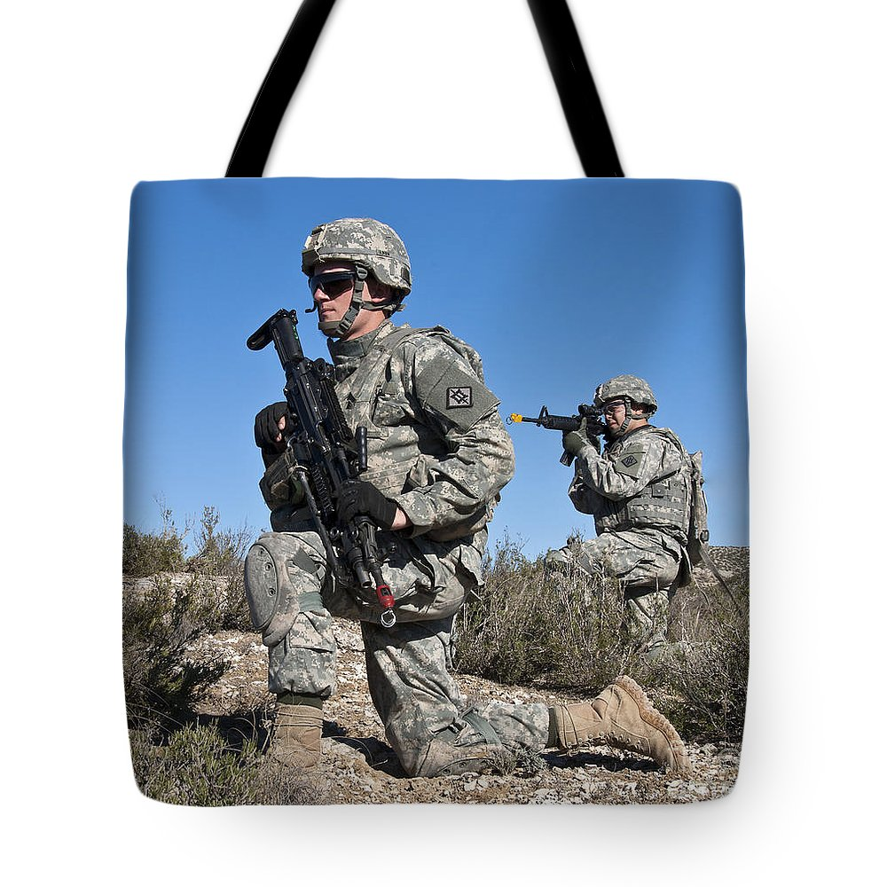 Military Tote Bag featuring the photograph U.s. Army Soldiers Scan The Terrain by Stocktrek Images
