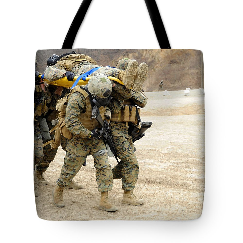 Us Armed Forces Tote Bag featuring the photograph U.s. Marines Carry A Fellow Marine by Stocktrek Images