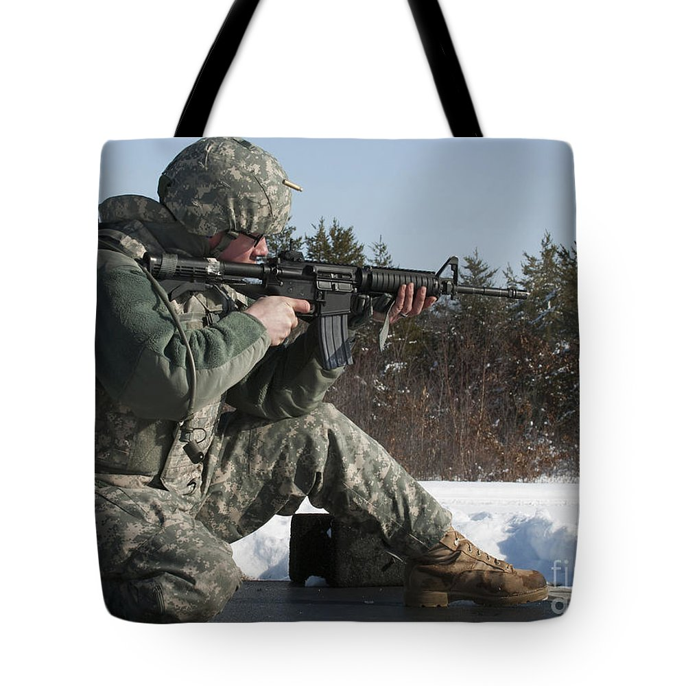 Fort Mccoy Tote Bag featuring the photograph U.s. Soldier Fires His M4a3 Carbine by Stocktrek Images