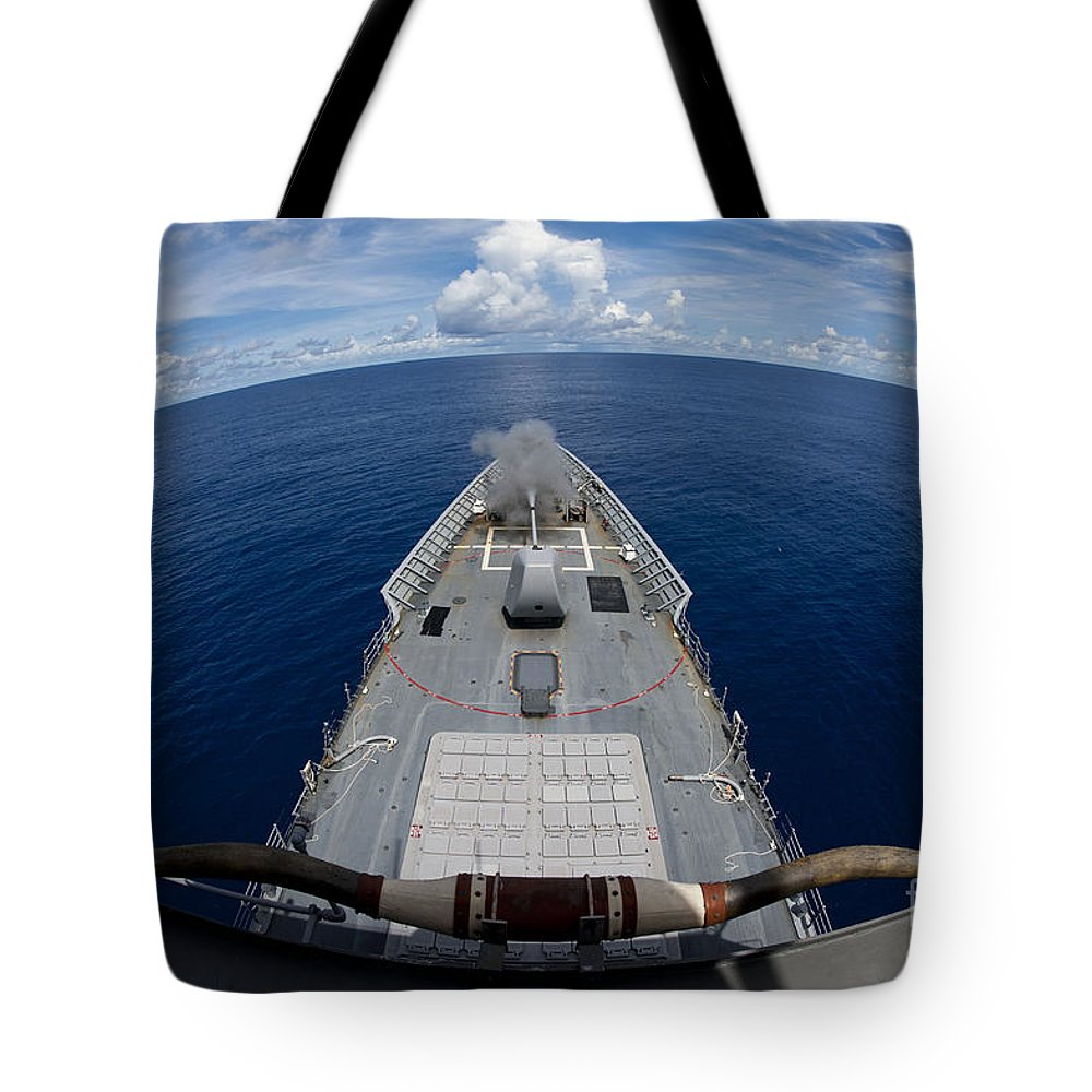 Us Navy Tote Bag featuring the photograph Uss Cowpens Fires Its Mk 45 Mod 2 Gun by Stocktrek Images