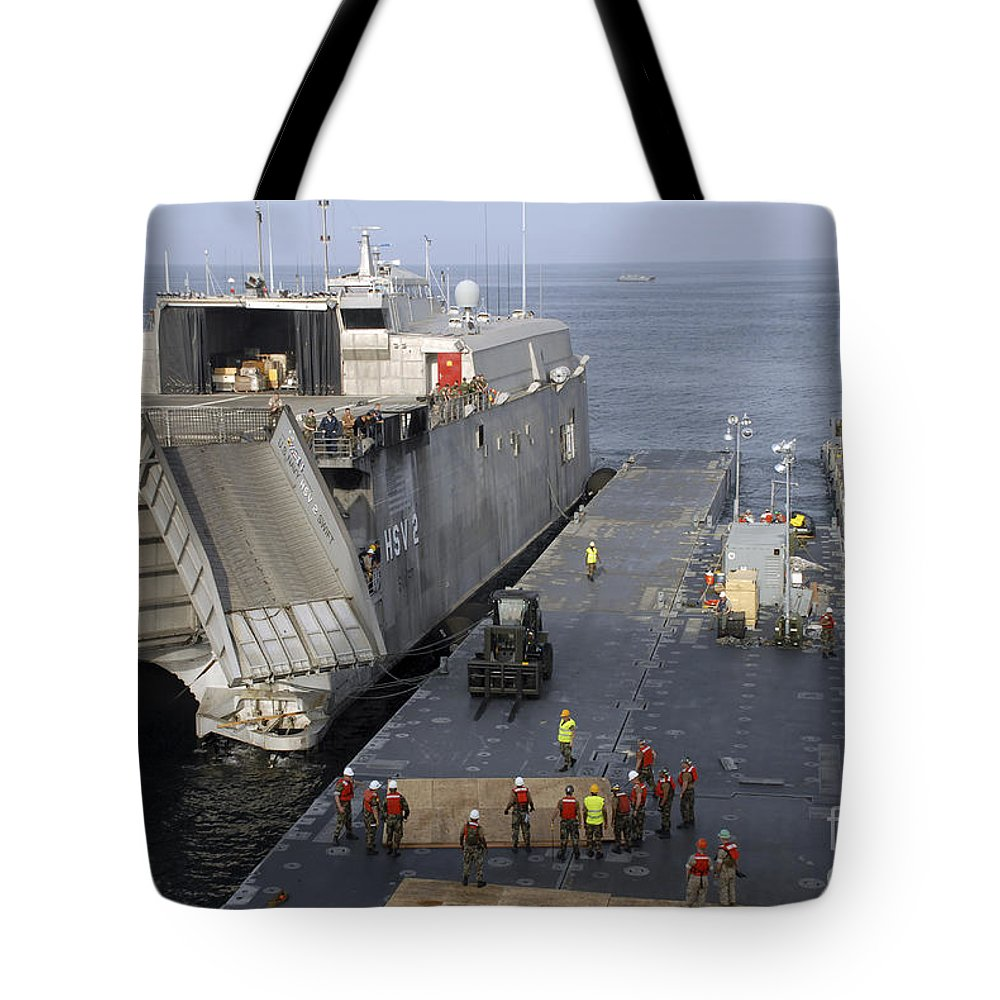 Africa Partnership Station Tote Bag featuring the photograph Vehicles Are Transferred Aboard by Stocktrek Images