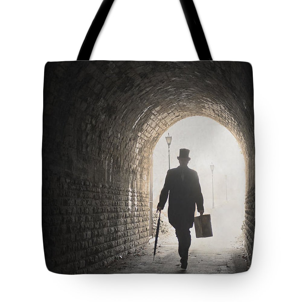 Man Tote Bag featuring the photograph Victorian Man With Top Hat And Case Walking Under A Bridge by Lee Avison
