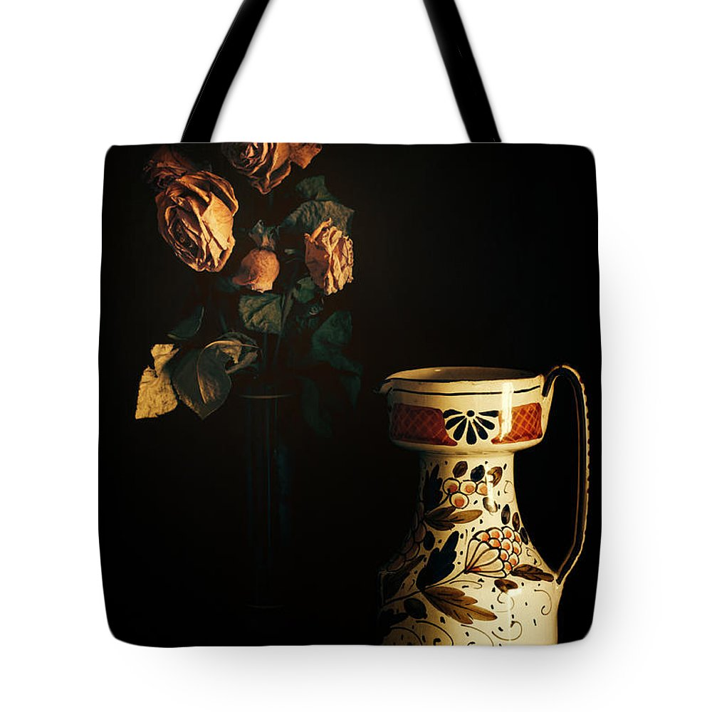 Chiaroscuro Tote Bag featuring the photograph Wilted Roses With Italian Vase by Silvia Ganora