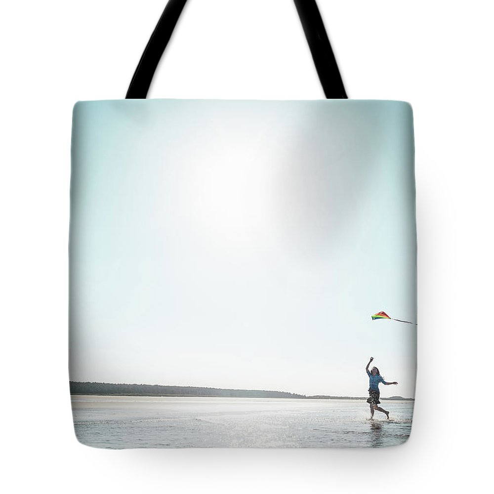 Three Quarter Length Tote Bag featuring the photograph Woman Flying Kite On Beach by Dan Brownsword