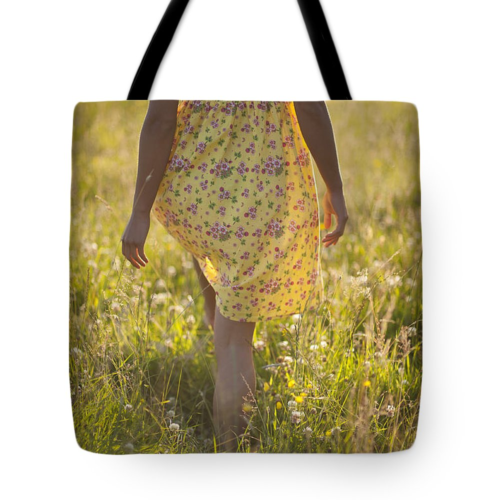 Girl Tote Bag featuring the photograph Woman In A Yellow Flowery Dress Walking In A Summer Meadow by Lee Avison