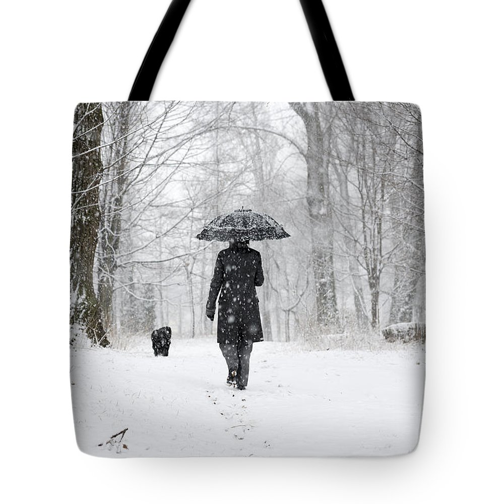 Path Tote Bag featuring the photograph Woman Walking In A Snowy Forest by Mats Silvan