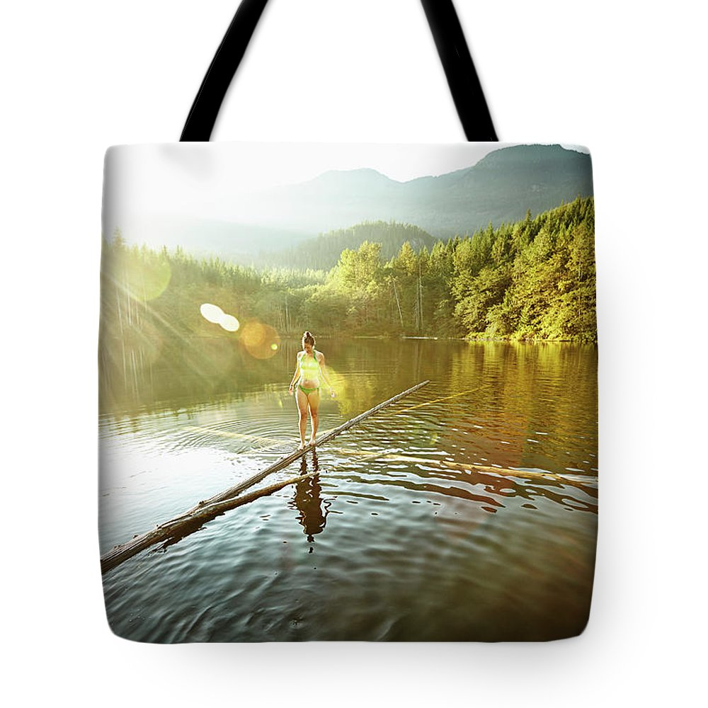 Pets Tote Bag featuring the photograph Woman Walking On Log In Alpine Lake by Thomas Barwick