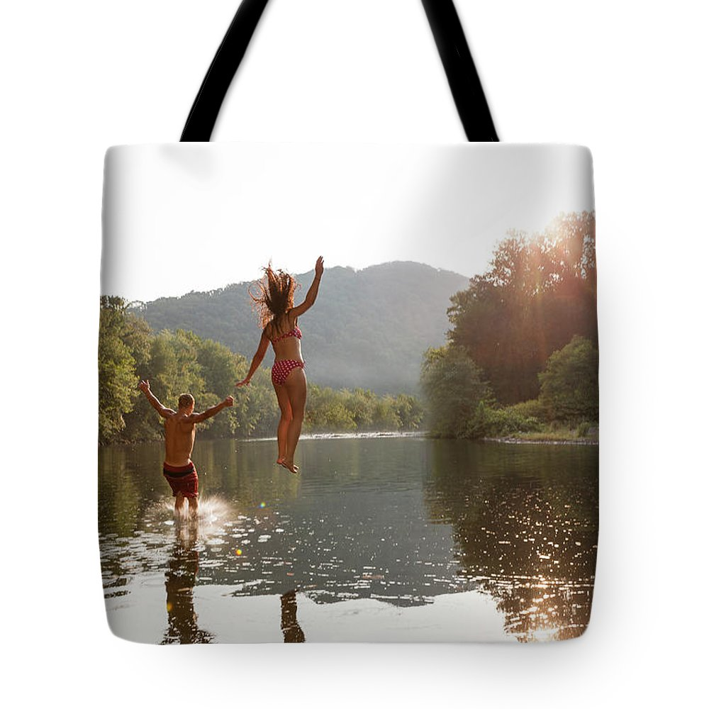 Young Men Tote Bag featuring the photograph Young Couple Jumping Into River by Zave Smith