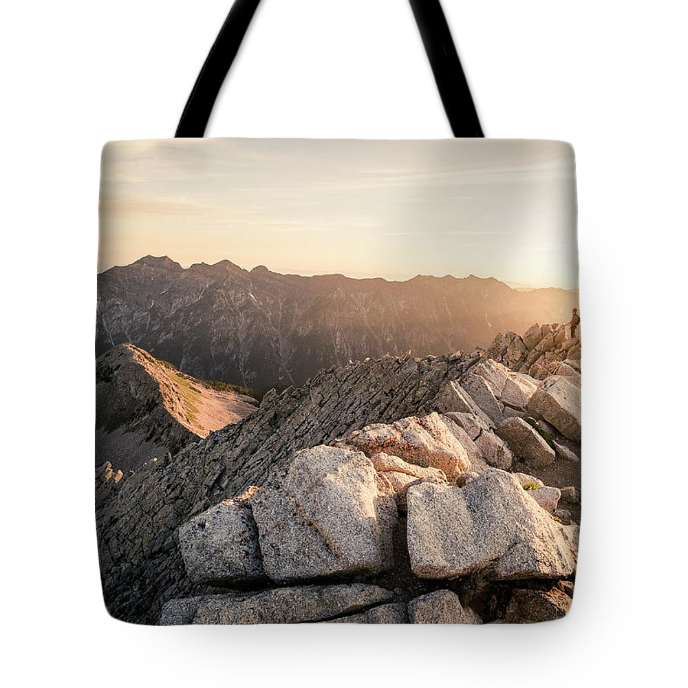 Exploration Tote Bag featuring the photograph Young Man Scrambles To The Summit by Conor Barry